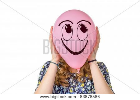 Girl holding pink balloon with smiling face