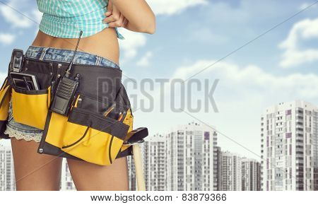 Woman in tool belt stands back. Buildings and sky as backdrop