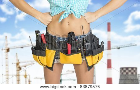 Woman in tool belt with different tools. Hands on hip