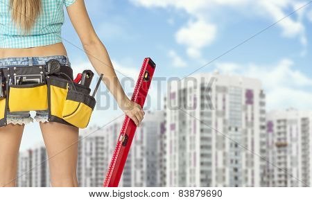 Woman in tool belt holding red building level. Buildings and sky as backdrop