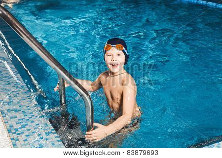 Young Boy Using Ladder To Exit Swimming Pool