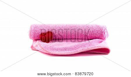 Pink Towel And Red Heart Rolled Up On A White Background