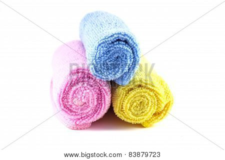 Red Yellow And Blue Towel Rolled Up On A White Background