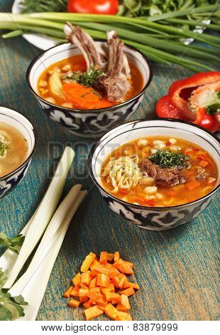Three Lagman And Shurpa Soups In Uzbek Bowls With Decor And Vegetables