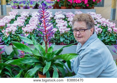 Senior woman showing flowering plant in shop
