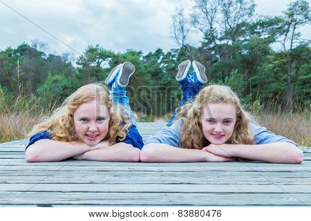 Two girls lying on wooden path in nature