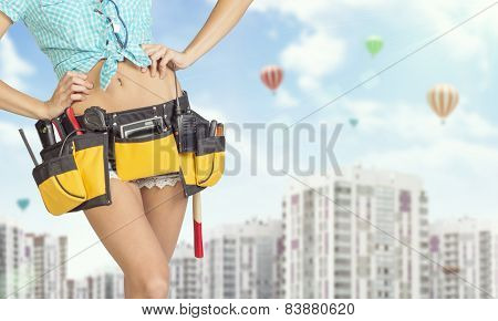 Woman in tool belt standing akimbo. Buildings and sky with air balloons on background