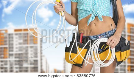 Woman in tool belt holding electrical cable. Buildings and sky on background