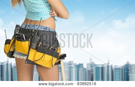 Woman in tool belt stands back. Building and sky as backdrop