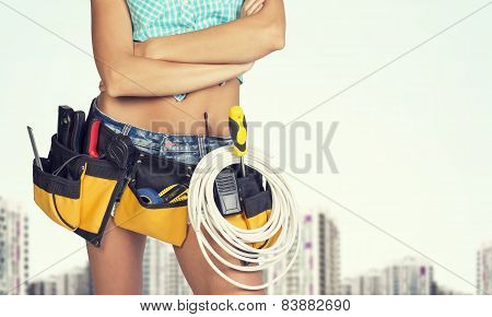 Woman in tool belt standing crossed arms. Cropped image. Buildings as backdrop