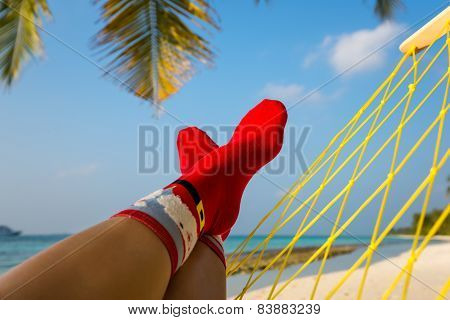 Woman Feet With Christmas Sock In Hammock On The Beach