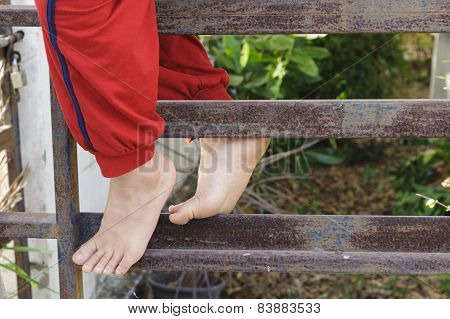 Kid Foot Climb On The Rust Iron Bar