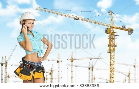 Woman in helmet and tool belt, talking on phone. Tower cranes as backdrop