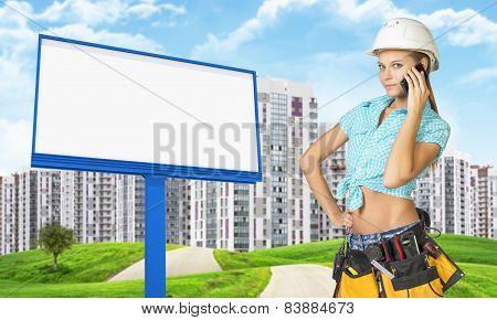 Woman in tool belt using phone. Green hills, road, buildings and billboard as backdrop