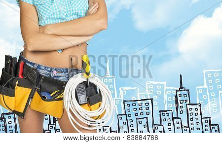 Woman in tool belt with different tools. Cropped image. Sketch buildings as backdrop