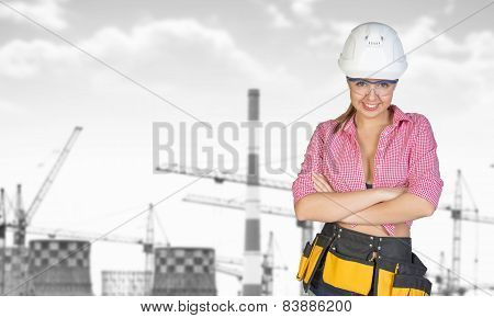 Woman in tool belt and helmet. Gray tower crane, chimneys as backdrop