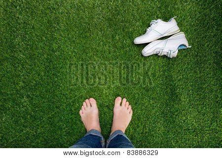 Feet Resting On Grass With Slying Sneakers