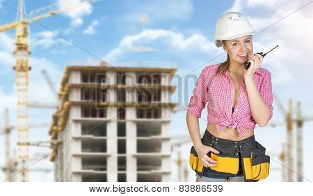 Woman in helmet and tool belt talking on portable radio. Construction site as backdrop