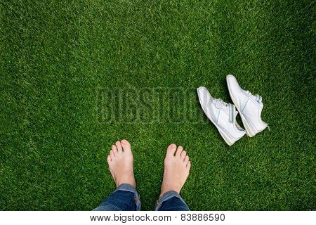 Feet Resting On Green Grass With Slying Sneakers