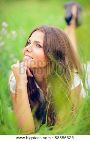 Happy Smiling Beautiful Young Girl Lying Among Grass And Flowers