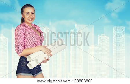 Woman in short jeans holding rolls of paper, smiling. Wire-frame buildings as backdrop