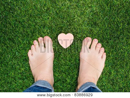 Feet Standing On Grass With Small Heart