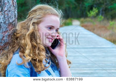 Blonde girl phoning mobile in nature