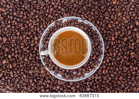 ceramic mug of cappuccino on a heap of roasted coffee beans