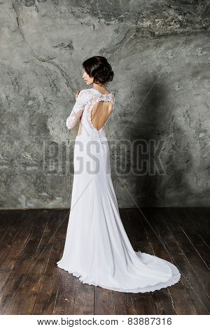 Back view of beautiful brunette bride with perfect makeup and hair style
