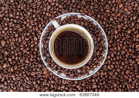 ceramic mug of drink coffee on a heap of roasted coffee beans