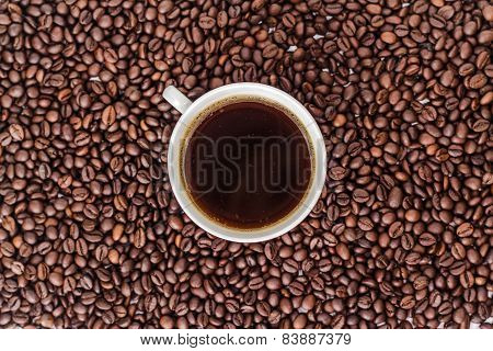 ceramic cup of drink coffee on a heap of roasted coffee beans
