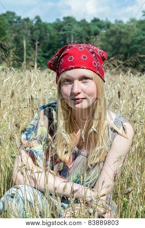 Blonde teenage girl sitting in cornfield