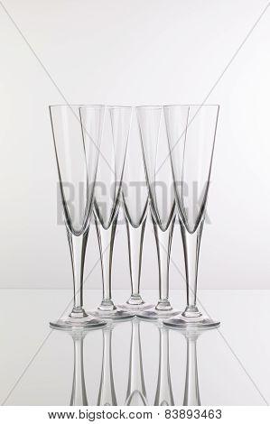 Five Champagne Glasses On A Glass Desk