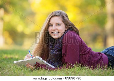 Female Teen On Ground Studying