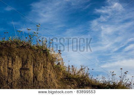 Blue Sky With Clouds Above A Grass Hillside