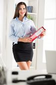 stock photo of short skirt  - Young pretty business woman in a short skirt holding a binder and with a smile looking at the camera - JPG