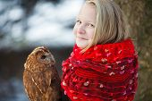 foto of snow owl  - Cute girl in red scarf standing with little owl in a park - JPG