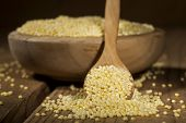 picture of millet  - Millet in a wooden bowl and spoon on a wooden background - JPG