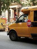 stock photo of bus driver  - Small school bus stops on the streets of a major city - JPG
