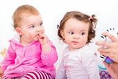 picture of teething baby  - Photo of two adorable baby sitting on the bed - JPG