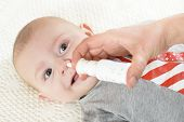 pic of snot  - Woman using nasal spray for a smiling baby - JPG