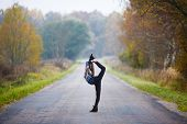 image of gymnastic  - Young professional gymnast makes splits on the road at autumn time - JPG