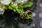 picture of infinity  - Two wedding rings in infinity sign with bouquet on black background - JPG
