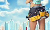 picture of framing a building  - Woman in tool belt with different tools stands back - JPG
