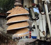 image of construction machine  - detail drilling machine boring holes in ground during construction road works - JPG
