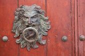 picture of flowing hair  - Large metal door knocker in the shape of a mans head with long flowing hair on a wooden door in the historic old city of Cartagena de Indias - JPG
