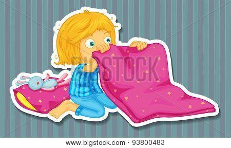 Girl in blue pajamas folding blanket