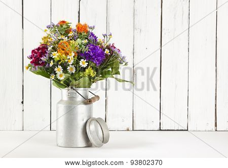 Summer flower bouquet in old milk churn in front of rustic wooden background