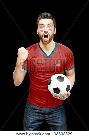 Chilean fan holding a soccer ball celebrates on black background