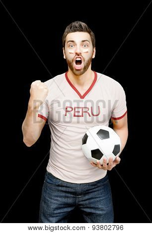 Peruvian fan holding a soccer ball celebrates on black background